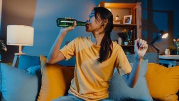gelukkige jonge aziatische vrouw die naar de camera kijkt, geniet van een nachtfeestevenement online met vrienden toast, drink bier via videogesprek online in de woonkamer thuis, blijf thuis quarantaine, sociaal afstandsconcept. foto