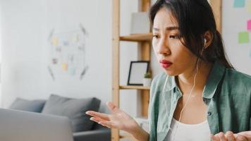 azië zakenvrouw met behulp van laptop praten met collega's over plan in video-oproep terwijl slim werken vanuit huis in de woonkamer. zelfisolatie, sociale afstand, quarantaine voor preventie van het coronavirus. foto