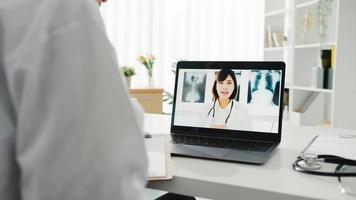 jonge aziatische dame arts in wit medisch uniform met behulp van laptop pratende videoconferentiegesprek met senior arts aan balie in gezondheidskliniek of ziekenhuis. sociale afstand, quarantaine voor het coronavirus. foto
