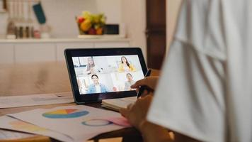 azië zakenvrouw met behulp van digitale tablet praten met collega over plan door video-oproep brainstorm online vergadering terwijl op afstand werken vanuit huis in de keuken. sociale afstand, quarantaine voor het coronavirus. foto