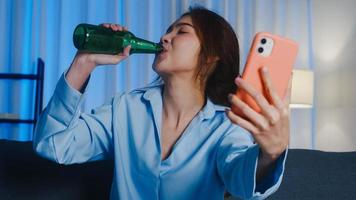jonge aziatische dame die bier drinkt met plezier gelukkig moment nachtfeest evenement online viering via videogesprek in de woonkamer thuis 's nachts. sociale afstand, quarantaine voor coronaviruspreventie. foto