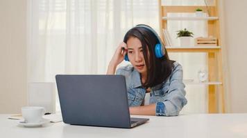 freelance zakelijke vrouwen vrijetijdskleding met behulp van laptop werkende videoconferentie met klant op de werkplek in de woonkamer thuis. gelukkig jong Aziatisch meisje ontspannen zittend op een bureau werk doen op internet. foto