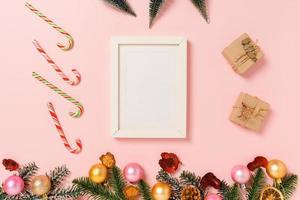 minimale creatieve platte lay van winterkerst traditionele compositie en nieuwjaarsvakantieseizoen. bovenaanzicht mockup zwarte fotolijsten voor tekst op roze achtergrond. bespotten en kopiëren van ruimtefotografie. foto
