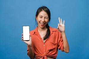 jonge aziatische dame toont een leeg smartphonescherm met positieve uitdrukking, glimlacht breed, gekleed in casual kleding en voelt zich gelukkig op een blauwe achtergrond. mobiele telefoon met wit scherm in vrouwelijke hand. foto