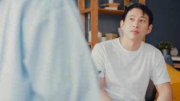 jonge azië vrouwelijke professionele arts arts die digitale tablet gebruikt die goed nieuws over gezondheidstests deelt met gelukkige mannelijke patiënt zit op de bank in huis. medische verzekering, bezoek patiënt thuis concept. foto