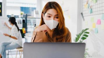azië zakenvrouw draagt gezichtsmasker voor sociale afstand in nieuwe normale situatie voor viruspreventie tijdens het gebruik van laptoppresentatie aan collega's over plan in videogesprek terwijl u op kantoor werkt. foto