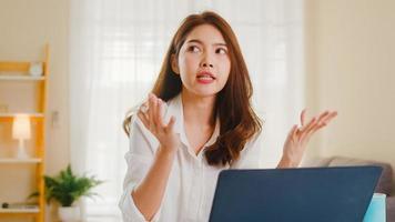 Aziatische zakenvrouw die laptop gebruikt, praat met collega's over het plan in een videogesprek terwijl ze slim vanuit huis in de woonkamer werkt. zelfisolatie, sociale afstand, quarantaine voor coronaviruspreventie. foto
