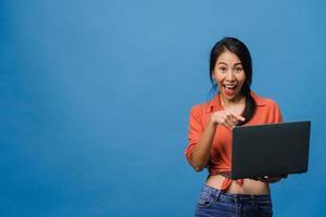 jonge aziatische dame die laptop gebruikt met positieve uitdrukking, breed glimlacht, gekleed in casual kleding die geluk voelt en geïsoleerd op blauwe achtergrond staat. gelukkige schattige blije vrouw verheugt zich over succes. foto