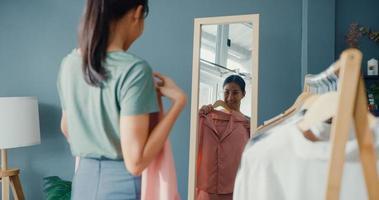 mooie aantrekkelijke aziatische dame die kleding kiest op een kledingrek dat zichzelf in de spiegel in de woonkamer in huis kijkt. meisje denk wat te casual shirt te dragen. levensstijl vrouwen ontspannen thuis concept. foto
