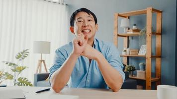 jonge Aziatische zakenman die computerlaptop gebruikt, praat met collega's over het plan in een videogesprekvergadering terwijl hij vanuit huis in de woonkamer werkt. zelfisolatie, sociale afstand, quarantaine voor het coronavirus. foto