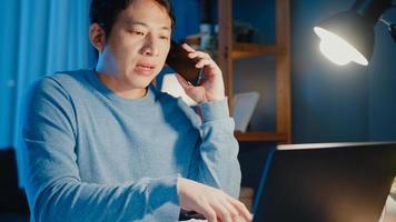 jonge azië zakenman gebruik smartphone oproep vergadering agenda opdracht papierwerk met collega kijken naar laptopcomputer in woonkamer thuis overuren 's nachts, werken vanuit huis corona pandemie concept. foto