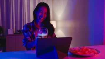 jonge azië dame bier drinken plezier gelukkig moment disco neon nacht feest evenement online viering via video-oproep in de woonkamer thuis. sociale afstand, quarantaine voor coronaviruspreventie. foto