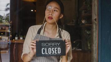 jong aziatisch managermeisje draait een bord van open naar gesloten bord op glazen deurcafé na quarantaine vanwege coronavirus. eigenaar klein bedrijf, eten en drinken, zakelijke financiële crisisconcept. foto
