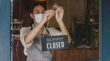 jong aziatisch meisje draagt een gezichtsmasker en draait een bord van gesloten naar open bord op de deur die naar buiten kijkt en wacht op klanten na afsluiting. eigenaar klein bedrijf, eten en drinken, bedrijf heropenen opnieuw concept. foto