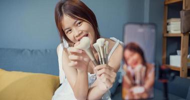 gelukkige jonge aziatische meisjesmake-upvlogger voorkant van telefooncamera geniet van beoordelingsgesprek met publiek in de woonkamer thuis. sociale afstand coronavirus pandemie concept. vrijheid en actieve levensstijl concept. foto