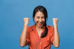 jonge aziatische dame met positieve uitdrukking, vrolijk en opwindend, gekleed in casual doek en kijk naar de camera over blauwe achtergrond. gelukkige schattige blije vrouw verheugt zich over succes. gezichtsuitdrukking concept. foto
