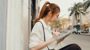 succesvolle jonge azië zakenvrouw in mode kantoorkleding met behulp van digitale tablet en tekstbericht typen terwijl ze 's ochtends alleen buiten in de stedelijke moderne stad zit. bedrijf onderweg concept. foto