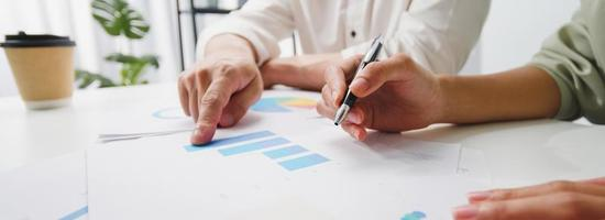 jonge Aziatische zakenmensen ontmoeten brainstormideeën over nieuw papierwerk projectcollega's werken samen plan successtrategie genieten van teamwork op kantoor. panoramische bannerachtergrond met exemplaarruimte. foto