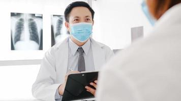 serieuze mannelijke arts in azië draagt een beschermend masker met behulp van klembord levert geweldig nieuws, bespreek resultaten of symptomen met vrouwelijke patiënt in het ziekenhuiskantoor. levensstijl nieuw normaal na corona virus. foto