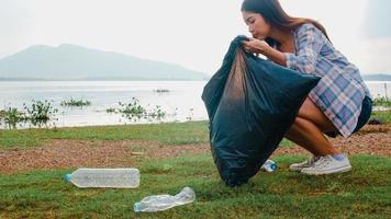 gelukkige jonge azië-activisten die plastic afval verzamelen op het strand. Koreaanse vrouwelijke vrijwilligers helpen de natuur schoon te houden en vuilnis op te halen. concept over milieubehoud vervuilingsproblemen. foto