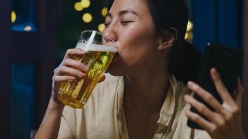 jonge azië dame bier drinken plezier gelukkig moment nacht feest nieuwjaar evenement online viering via video-oproep per telefoon thuis 's nachts. sociale afstand, quarantaine voor coronaviruspreventie. foto