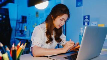 freelance azië dame met behulp van telefoon hard werken op nieuw normaal thuiskantoor. 's nachts thuiswerken, werken op afstand, zelfisolatie, sociale afstand, quarantaine voor preventie van het coronavirus. foto