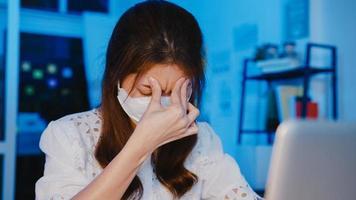 freelance azische vrouwen dragen gezichtsmasker met behulp van laptop hard werken op een nieuw normaal thuiskantoor. 's nachts werken vanuit huis overbelasting, zelfisolatie, sociale afstand, quarantaine voor preventie van het coronavirus. foto