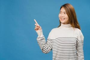 portret van een jonge aziatische dame die lacht met een vrolijke uitdrukking, toont iets geweldigs op lege ruimte in casual kleding en staat geïsoleerd op een blauwe achtergrond. gezichtsuitdrukking concept. foto