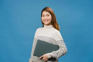 verraste jonge aziatische dame houdt laptop vast met positieve uitdrukking, glimlach breed, gekleed in casual kleding en kijkt naar camera op blauwe achtergrond. gelukkige schattige blije vrouw verheugt zich over succes. foto