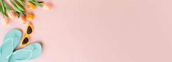 creatieve platte lay van reizen vakantie lente of zomer tropische mode. bovenaanzicht strandaccessoires op pastelroze kleur achtergrond. panoramische banner met kopieerruimte voor tekst en reclamegebied. foto