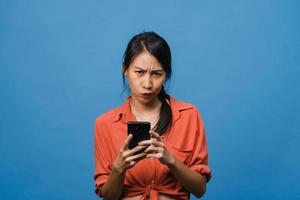 denken dromende jonge azië dame met behulp van telefoon met positieve uitdrukking, gekleed in casual kleding geluk voelen en staan geïsoleerd op blauwe achtergrond. gelukkige schattige blije vrouw verheugt zich over succes. foto
