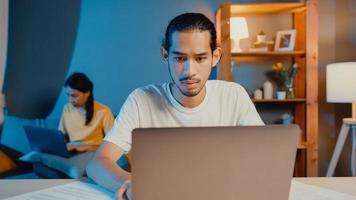 freelance azië paar man en vrouw in casual voelen serieuze focus op werk aparte laptopcomputer 's nachts, hasband zit vooraan op tafel vrouw zit achter op de bank thuis. werk vanuit huis concept. foto