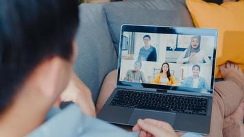 jonge Aziatische zakenman die laptop gebruikt, praat met collega's over het plan in een videogesprekvergadering terwijl hij vanuit huis in de woonkamer werkt. zelfisolatie, sociale afstand, quarantaine voor preventie van het coronavirus. foto