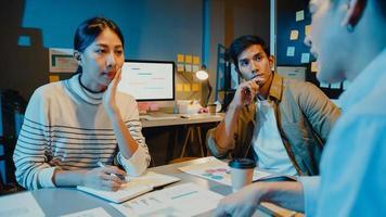 gelukkige jonge Aziatische zakenlieden en zakenvrouwen die brainstormen over een aantal nieuwe ideeën over het project aan zijn partner die samenwerken bij het plannen van successtrategie geniet van teamwork in een klein modern nachtkantoor. foto