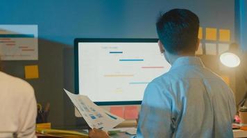gelukkige azië zakenman sociale afstand in nieuwe normale situatie voor viruspreventie tijdens het gebruik van laptop online zakelijke overuren terug op het werk in de kantoornacht. leven en werken na het coronavirus. foto