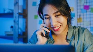 freelance azische vrouwen die laptop gebruiken praten aan de telefoon drukke ondernemer die op afstand in de woonkamer werkt. 's nachts thuiswerken, werken op afstand, sociale afstand, quarantaine voor coronavirus. foto