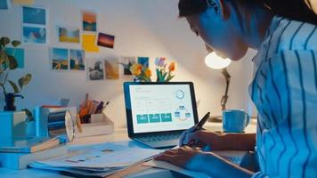 jonge azië zakelijke dame freelance focus op laptop schrijf werkblad financiën grafiek rekening grafiek marktplan in laptop en tablet 's nachts. studente leert online, werk vanuit huis concept. foto