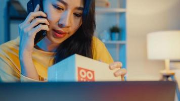 jonge aziatische vrouw belt smartphone praat met klant voor cheque bevestig bestelling in voorraad op laptopcomputer in thuiskantoor 's nachts. klein bedrijf, online marktlevering, lifestyle freelance concept. foto