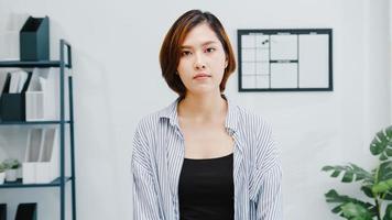 portret van mooie executive zakenvrouw slimme vrijetijdskleding camera kijken en glimlachen, gelukkig in moderne kantoor werkplek. jonge aziatische dame praat met collega in videogesprek thuis. foto