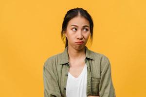 portret van jonge Aziatische dame met negatieve uitdrukking, opgewonden schreeuwen, huilen emotioneel boos in casual kleding geïsoleerd op gele achtergrond met lege kopie ruimte. gezichtsuitdrukking concept. foto