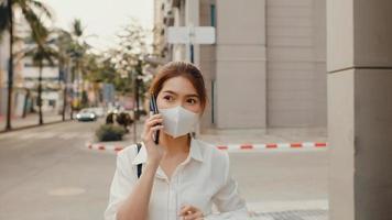 succesvolle jonge Aziatische zakenvrouw in mode-kantoorkleding draagt een medisch gezichtsmasker dat via de mobiele telefoon praat terwijl ze 's ochtends alleen buiten in de stedelijke moderne stad loopt. bedrijf onderweg concept. foto