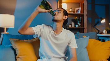 gelukkige jonge aziatische man die naar de camera kijkt geniet van een nachtfeestevenement online met vrienden toast bier drinken via videogesprek online in de woonkamer thuis, thuisblijven quarantaine, sociaal afstandsconcept. foto
