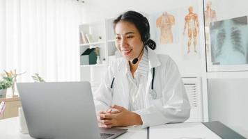 jonge Aziatische dame arts in wit medisch uniform met stethoscoop met behulp van computerlaptop praten videoconferentiegesprek met patiënt aan balie in gezondheidskliniek of ziekenhuis. advies- en therapieconcept. foto
