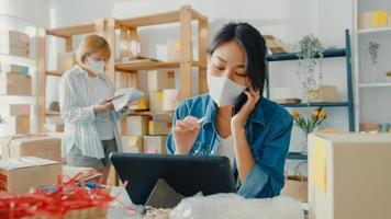 jonge Aziatische zakenvrouwen dragen een gezichtsmasker met behulp van een mobiel telefoontje dat een inkooporder ontvangt en controleren of het product op voorraad werkt op het thuiskantoor. eigenaar van een klein bedrijf, freelance concept voor online marktlevering. foto