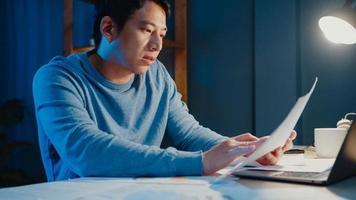 Aziatische freelance zakenman focus werktype op laptopcomputer bezig met vol papierwerk grafiek op bureau in woonkamer thuis overuren 's nachts, werk vanuit huis tijdens covid-19 pandemie concept. foto