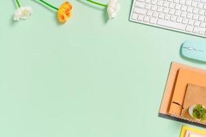 minimale werkruimte - creatieve platliggende foto van werkruimtebureau. bovenaanzicht bureau met toetsenbord, muis en notebook op pastel groene kleur achtergrond. bovenaanzicht met kopieerruimte, platliggende fotografie.