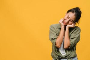 portret van jonge Aziatische dame met positieve uitdrukking, breed glimlachen, gekleed in casual kleding op gele achtergrond. gelukkige schattige blije vrouw verheugt zich over succes. gezichtsuitdrukking concept. foto