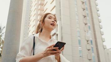 succesvolle jonge azië zakenvrouw in mode kantoorkleding die op de weg een taxi neemt en een smartphone gebruikt terwijl ze buiten in de stedelijke moderne stad staat. bedrijf onderweg concept. foto