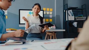 gelukkige jonge Aziatische zakenlieden en zakenvrouwen die brainstormen over een aantal nieuwe ideeën over het project aan zijn partner die samenwerken bij het plannen van successtrategie geniet van teamwork in een klein modern kantoor aan huis. foto