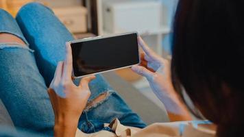 jonge aziatische dame gebruikt een smartphone met een leeg zwart scherm mock-up display voor reclametekst terwijl ze op de bank in de woonkamer op de moderne huisnacht rust. chroma key-technologie, marketing ontwerpconcept. foto